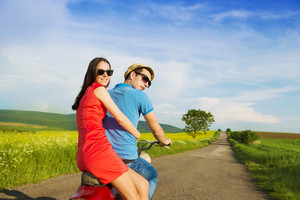 Happy young couple in love on retro motorbike driving togetger and ejoying the trip in green field