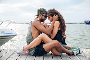 Happy young couple in love sitting and kissing at the wooden sea pier