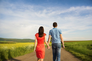 Happy young couple in love walking and holding hands on countryside road next to the colza field