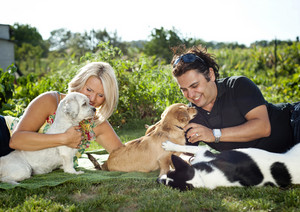 Happy young couple is laying down on grass and playing with their dogs