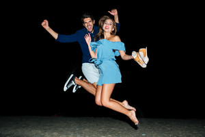 Happy young couple jumping in the air on the beach at night