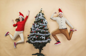 Happy young couple next to the Christmas tree against the beige background