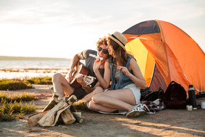 Happy young couple playing guitar and eating fryed marshmallows near touristic tent
