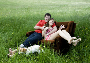 Happy young couple relaxing and having fun on the couch at the green field