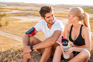 Happy young couple resting together with bottle of water outdoors