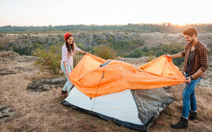 Happy young couple setting a tent outdoors