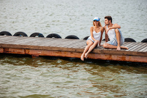 Happy young couple sitting and talking on pier