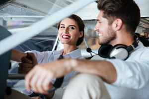 Happy young couple sitting in cabine of small airplane