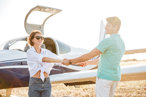 Happy young couple smiling and holding hands on runway near small plane
