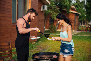 Happy young couple standing and cooking meet on barbeque grill outdoors