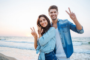 Happy young couple standing and showing peace sign on the beach