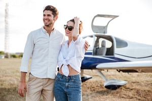 Happy young couple standing in front of small private airplane