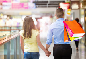 Happy young couple with bags in shopping mall