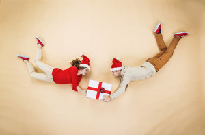 Happy young couple with Christmas presents flying against the beige background
