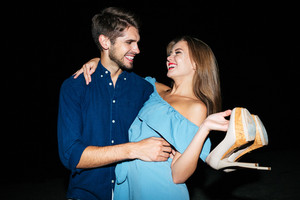 Happy young couple with shoes in hands hugging and laughing at night