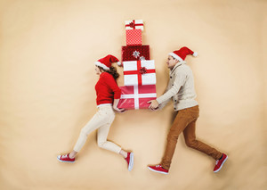 Happy young couple with stack of Christmas presents against the beige background