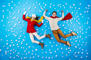 Happy young couplein winter clothes having fun against the blue background with snowflakes