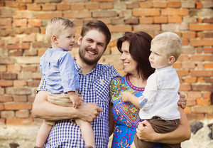 Happy young family have fun together in nature by the old brick house