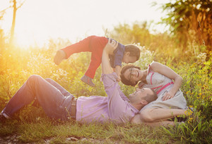 Happy young family having fun outside in summer nature