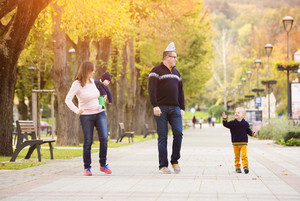 Happy young family on a walk in autumn city park