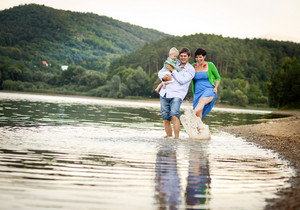 Happy young family spending summer time together by the lake on the sandy beach