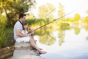 Happy young father fishing on the lake with his little daughter