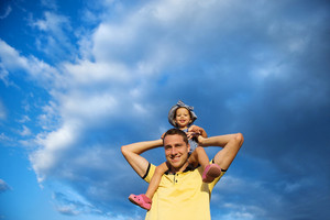 Happy young father holding his little daughter on shoulders against blue sky