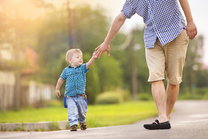 Happy young father holding his little son's hand and walking on road