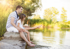 Happy young father sitting by the lake with his little daughter