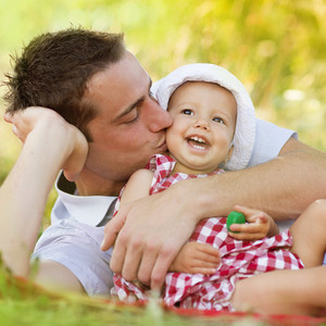 Happy young father spending time outdoor on a summer day with his beautiful daughter