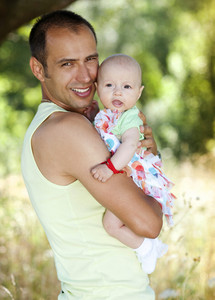 Happy young father spending time with his baby daughter in green nature.