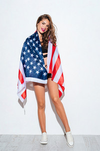Happy young girl holding USA flag in bikini isolated on a white background
