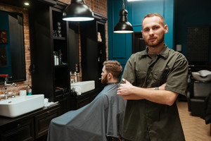 Happy young hairdresser standing near his client. Looking at camera.