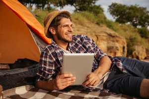 Happy young handsome man using tablet computer while lying at the beach