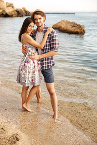 Happy young hipster couple in love standing at the beach and hugging