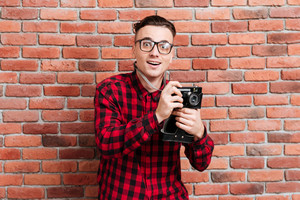 Happy young hipster in glasses standing near the wall with retro camera