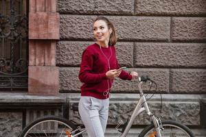 Happy young lady walking with her bicycle in the city while standing near wall and listen to music by her phone. Look aside.