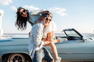 Happy young man carrying his woman in front of vintage cabriolet