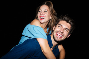 Happy young man holding girlfriend on his back at night