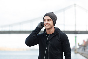 Happy young man in hat and gloves listening to music with earphones outdoors