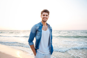 Happy young man in jeans shirt standing and smiling on the beach