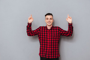 Happy young Man in shirt pointing up and looking at camera. Isolated gray background
