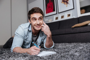 Happy young man making notes while talking on mobile phone on carpet at home
