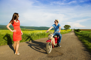 Happy young man on retro motorbike is picking up beautiful girl in red dress