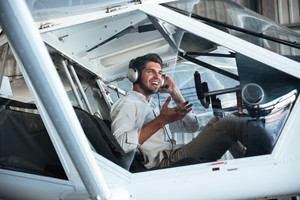 Happy young man pilot sitting in small