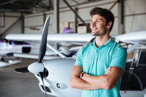 Happy young man standing with arms crossed near small airplane