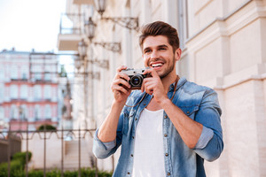 Happy young man taking pictures with vintage photo camera on the street