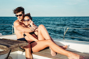 Happy young married couple in love resting together on the yacht