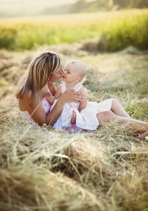 Happy young mother having fun with her little daughter in summer nature