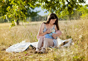 Happy young mother is feeding her baby boy in nature